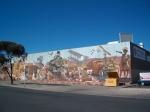 De geschiedenis van Australië speels afgebeeld op een muurschilderij van een warenhuis in Alice Springs.