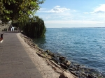 Zicht op het gardameer vanaf Garda's brede boulevard, Lungolago. Die is populair bij Italianen en toeristen om lekker te flaneren, flirten en luieren.