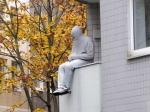 Nee, deze gast zit niet in straf op het balkon. Het is een kunstwerk op de Brusselse plaats.