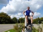 Simon poseert op monument van René Pottier die in 1906 de ronde van Frankrijk won.