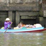 Een verkoopster op haar platbodem bootje in de Klongs van Thon Buri probeert haar waren te verkopen.