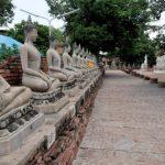 Rij met gerestaureerde Boeddhabeelden in de Wat Yai Chai Mongkom. Deze waren door de Khmer onthoofd in hun zoektocht naar goud.