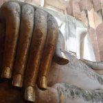 De grote zittende Boeddha van de Wat Si Chum tempel heeft een vergulde rechterhand.