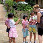 Maddy deelt snoepjes, zeepjes en ballonnen uit aan de kinderen van de rode Karen.