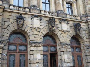 Politiegebouw met boven de ingangen allegorische afbeeldingen van een politieagent, vrouwe justicia en een boef.